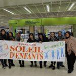 groupe de mamans de l'association qui tient une bannière avec le logo de l'association