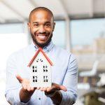 homme noir heureus tient une maison dans ses mains